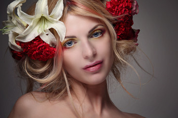 Portrait of a girl model with beautiful hair and flowers in her