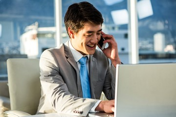 Smiling asian businessman talking on the phone