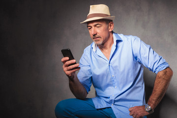 man pose in studio background while looking at a phone