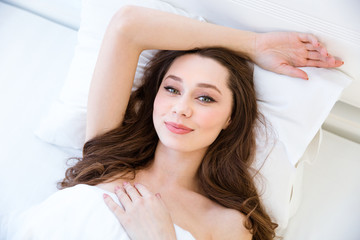 Tender charming woman relaxing in bed