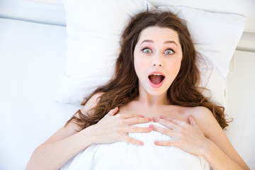 Amazed beautiful young woman wake up in bed