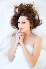 Playful woman lying in bed and touching her lips
