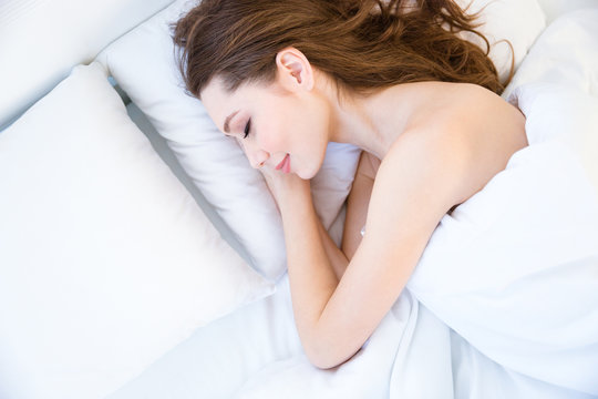 Top view of tired beautiful young woman sleeping on bed