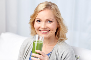 happy woman drinking green juice or shake at home