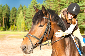 Girl equestrian riding horseback and stroking horse neck. Summer
