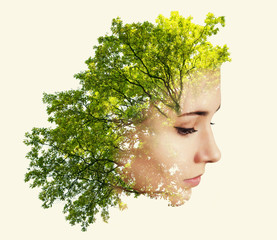 Double exposure portrait of young woman and tree branches with leaves.