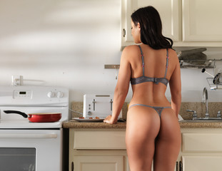 sexy girl wearing lingerie cooking bacon  in kitchen