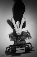Young woman in black dress lies near a typewriter.