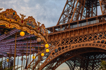 Close-up elements part of Eiffel tower in Paris against dramatic twilight sky at evening summer time.