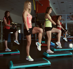Young pretty women exercising on step boards in aerobics class. Fitness people working out with steppers in the gym.