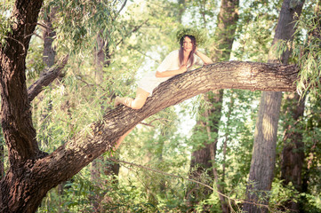 Beautiful woman lying  on tree in forest.