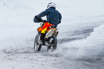 racer motorcycle rides on motocross snowy track in winter. rear view. gravel from under wheels