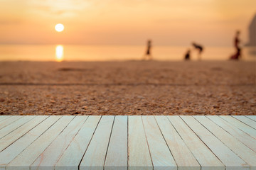Empty top view of wooden table and view of sunset or sunrise on san beach background.