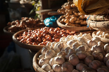 Baskets with garlic and onions under morning light at the street market, Nha Trang, Vietnam.