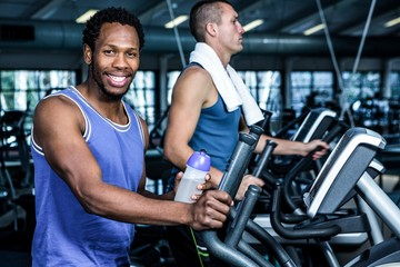 Smiling man using elliptical machine