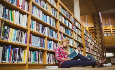 Smiling classmates reading book while leaning on bookshelves