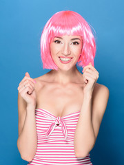 Portrait of beautiful smiling young woman with pink hair on a blue background