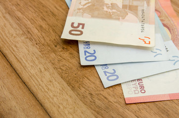 different euro banknotes on wooden table
