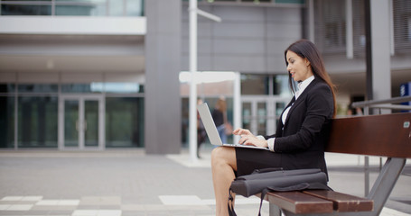 Side view of business woman sitting alone on bench with bag and using laptop computer near building