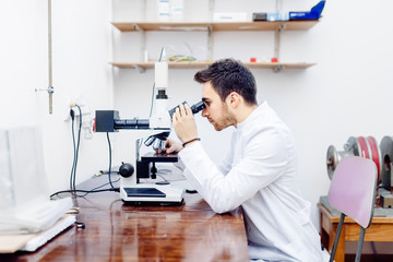 scientist with microscope, examining samples and contaminated probes in special laboratory