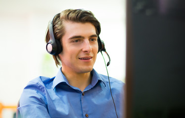 Young customer service operator talking on headset, smiling.