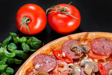 closeup Tasty pizza with tomatoes, mushroom, sausage, basil and