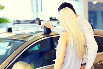 couple buying car in auto show or salon
