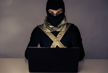 Terrorist working on his computer.