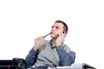 office worker. Man sitting at a desk with a pen in his mouth and talking on the phone