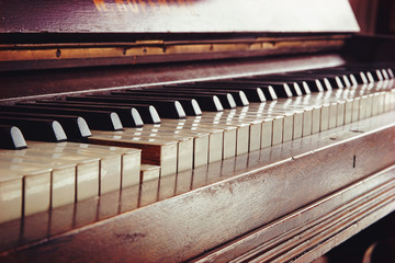old piano keyboard, one key is pressed, music concept in warm co