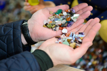 Colored stones in his hands. Round precious and semi-precious minerals.Polished minerals. Beautiful natural stones. People with hand sorted stones. Geology and geography.  A scattering of stones.
