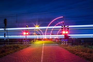 Bewaakte spoorwegovergang met brandende lichten in de nacht en voorbijrijdende trein