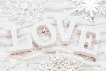 Word LOVE on white fabric background with engagement diamond ring. Good for Valentine's day cards.