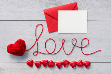 "Word ""love"" and red envelope with letter on a wooden background. Valentines Day background"
