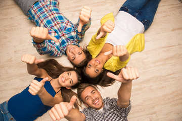 Cheerful young people lying on the floor showing thumbs up