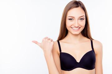 Pretty girl in black bra pointing away