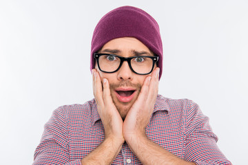 Surprised man in hat and glasses touching his face