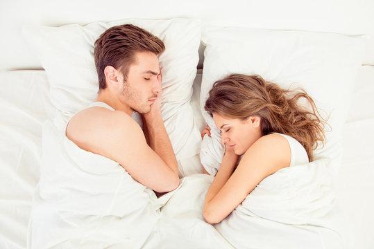 Beautiful couple sleeping together in bedroom