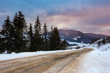 mountain road in snow near the coniferous forest with cloudy eve