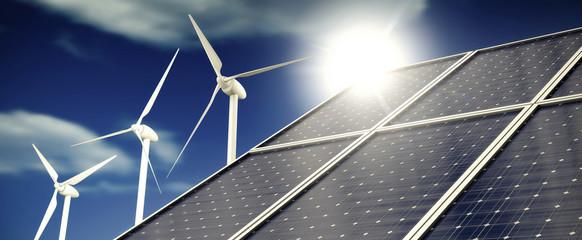 Sonnenkollektoren und Windkraftanlagen vor blauem Himmel mit Wolken im Sonnenlicht