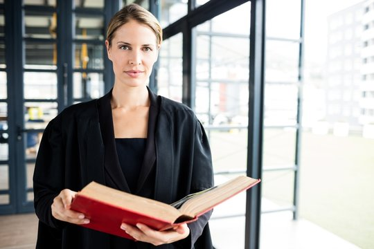 Female lawyer reading a book attentively