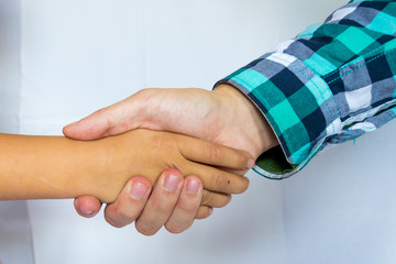 Adult and child holding hands of different color and race together to help