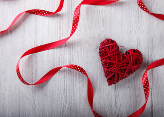 Gift and the heart is decorated with a red ribbon for a romantic Valentine's day celebration, on a light background.selective focus.
