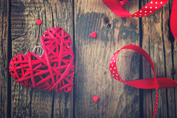 Heart decorated with a red ribbon for a romantic Valentine's day celebration, on vintage wooden background.Toned image.Vintage style.selective focus.
