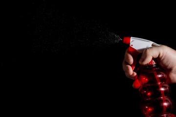 human hand with a spray gun sprays water on a dark background
