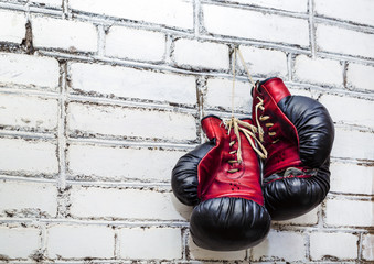 Fototapeta A pair of old boxing gloves hanging on white brick wall background. obraz