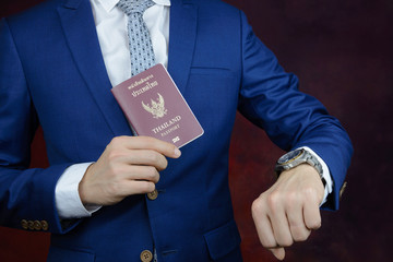 businessman showing passport, check time on watch