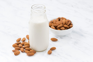 almond milk in a glass bottle on white table