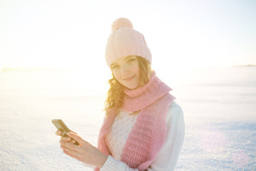 Young  woman with smart phone and winter landscape