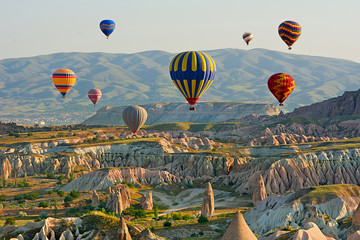 Colorful hot air balloons flying over the valley at Cappadocia Wall mural
